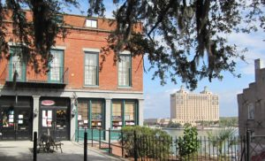View on Ye Ole Tobacco shop from River Street Inn parking lot looking towards river with Westin Savannah in background.